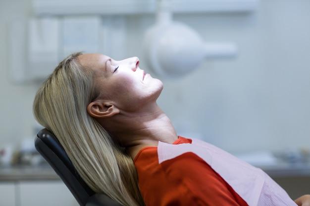Frau, die auf zahnarztstuhl entspannt