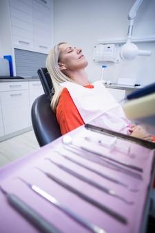 Frau, die auf zahnarztstuhl mit zahnärztlichen werkzeugen auf vordergrund entspannt