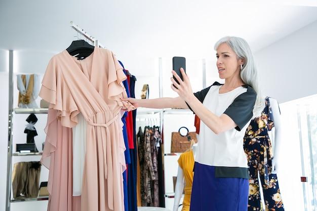 Frau, die auf zelle im modegeschäft spricht und kleid auf gestell an der vorderseite zeigt. mittlerer schuss. boutique-kunden- oder kommunikationskonzept