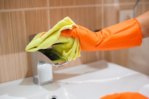 Frau, die aufgaben im badezimmer, reinigungshahn tut.