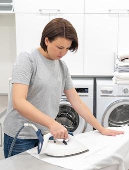 Frau, die aufgaben in der waschküche mit waschmaschine tut