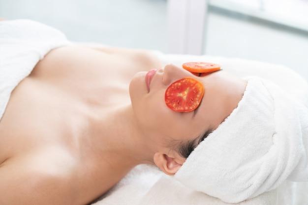 Frau, die augennaturbehandlung durch tomate erhält.