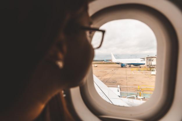 Frau, die aus flugzeugfenster heraus dem flughafen betrachtet