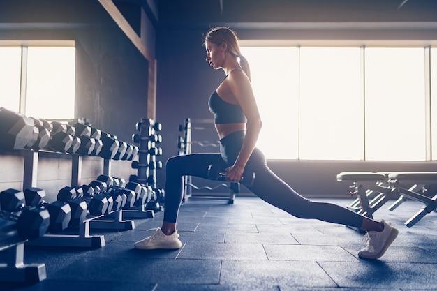 Frau, die ausfallschritte übung mit hanteln im fitnessstudio tut.