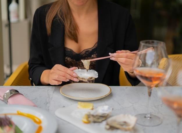Frau, die austern mit stäbchen isst, die am tisch vor dem restaurant sitzen. konzept des luxus