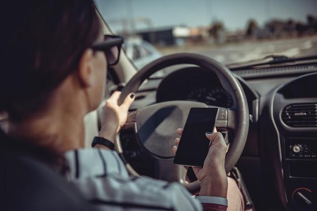 Frau, die auto fährt und intelligentes telefon verwendet