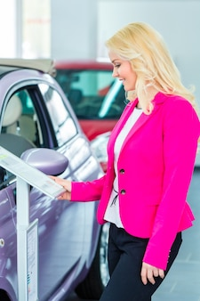 Frau, die auto für kauf im autohaus wählt