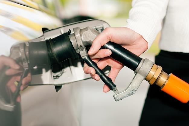 Frau, die auto mit flüssiggas tankt