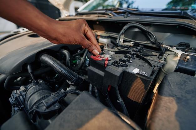Frau, die autobatterie prüft