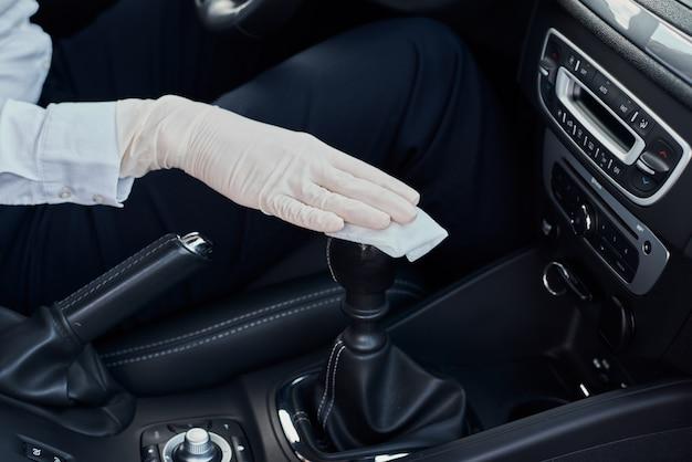 Frau, die autoinnenraum reinigt. hand mit antibakteriellem wischtuch desinfizieren auto