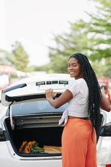 Frau, die autokofferraum schließt