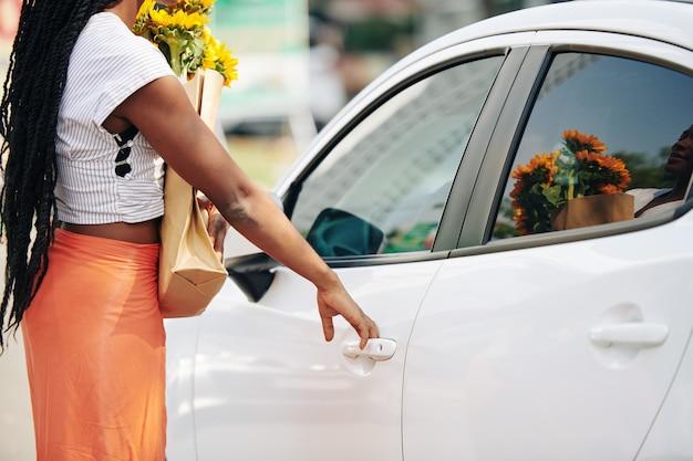 Frau, die autotür öffnet
