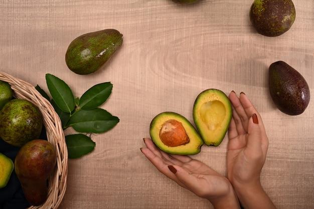 Frau, die avocado auf hölzernem hintergrund hält.