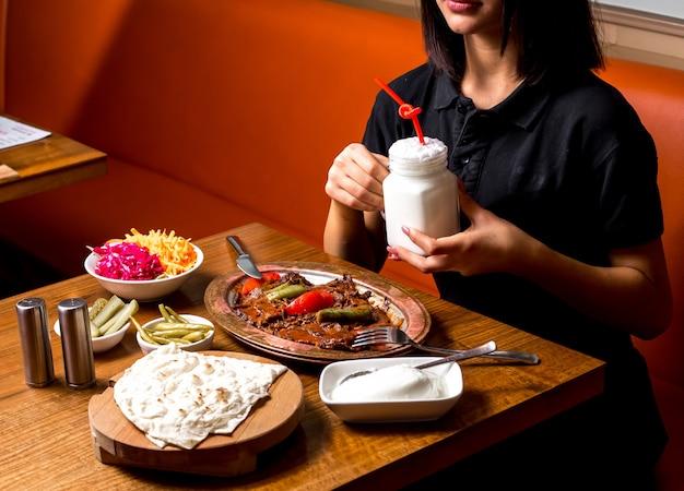 Frau, die ayranbecher hält, der mit iskender kebab in der kupferplatte gedient wird