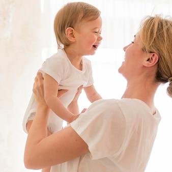 Frau, die baby hält und lächelt