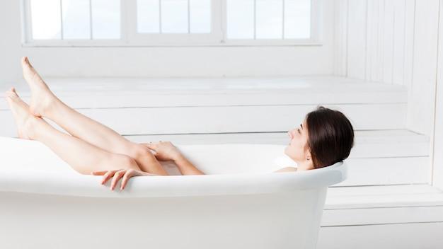 Frau, die bad im minimalistic innenraum nimmt
