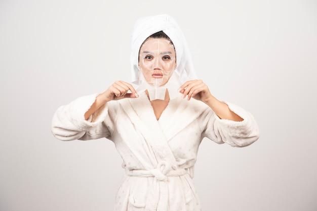 Frau, die bademantel und handtuch mit gesichtsmaske trägt