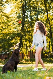 Frau, die ball mit ihrem hund im garten spielt