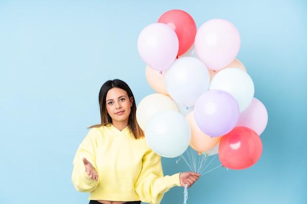 Frau, die ballone in einer partei über dem blauen wandhändeschütteln nach viel hält