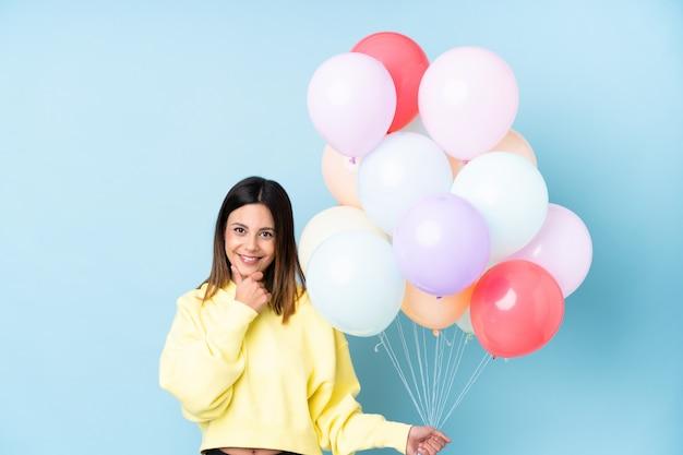 Frau, die ballone in einer partei über dem lokalisierten blauen wandlachen hält