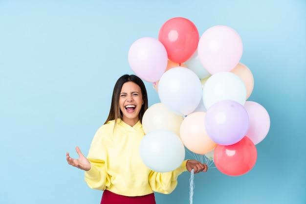 Frau, die ballone in einer partei über lokalisierter blauer wand unglücklich und mit etwas frustriert hält