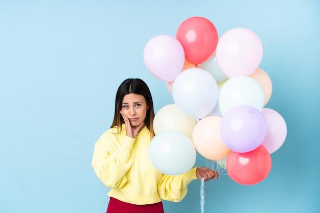 Frau, die ballone in einer partei unglücklich und frustriert hält