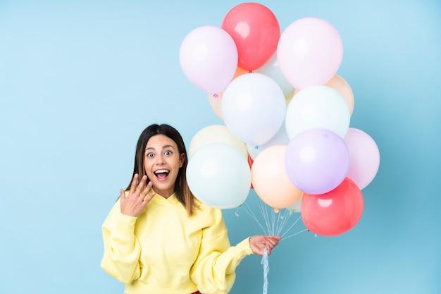 Frau, die ballone in einer party mit überraschungsgesichtsausdruck hält