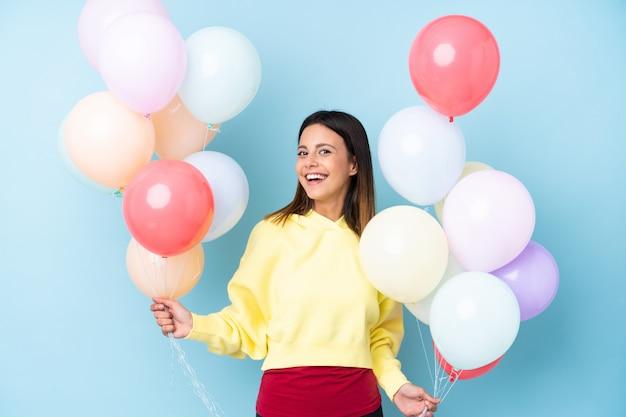 Frau, die ballone in einer party über lokalisierter blauer wand hält