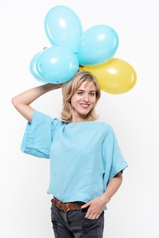 Frau, die ballone über ihrem kopf hält