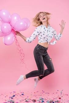 Frau, die ballone und das springen hält
