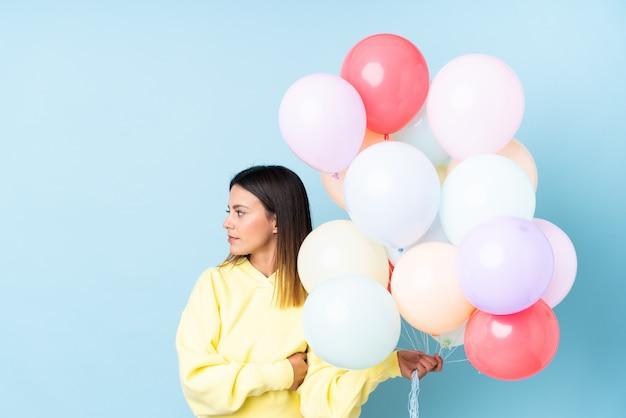 Frau, die ballons in einer partei über lokalisierter blauer wand schaut seite hält