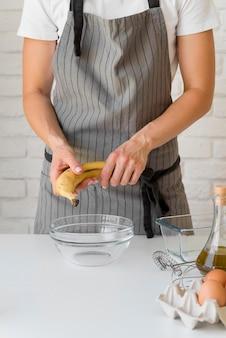 Frau, die banane über schüssel hält