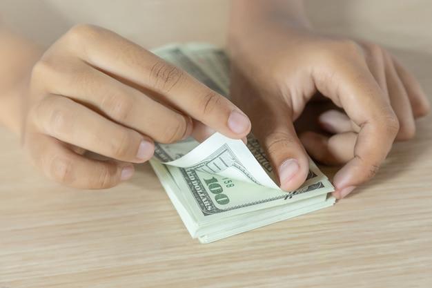 Frau, die banknoten auf tisch zählt