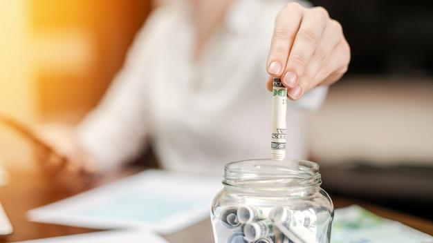 Frau, die banknoten in ein glas mit gerollten banknoten auf dem tisch fallen lässt. papiere auf dem tisch