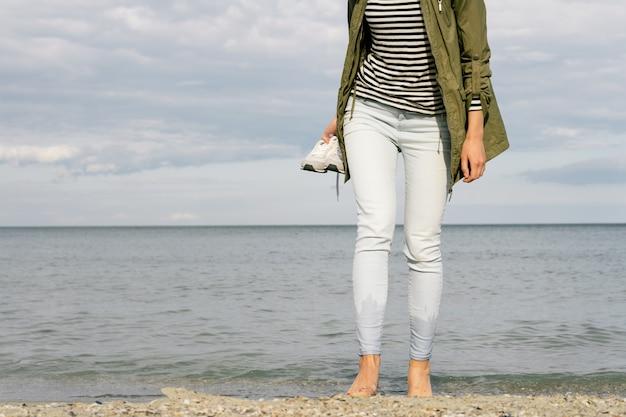 Frau, die barfuß auf den strand geht und in der hand einen schuh hält