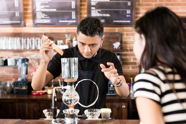 Frau, die barista aufpasst, tropfenfängerkaffee im café zuzubereiten