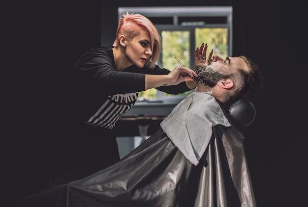 Frau, die bart des mannes im salon rasiert
