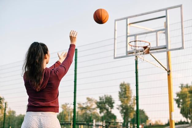 Frau, die basketball allein mit kopienraum spielt