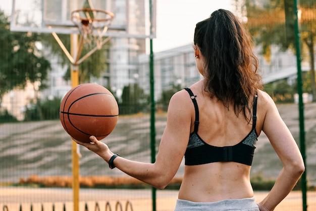 Frau, die basketball allein spielt