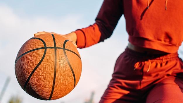 Frau, die basketball draußen spielt