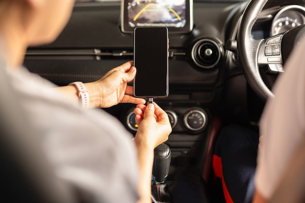 Frau, die batterie smartphone im auto auflädt