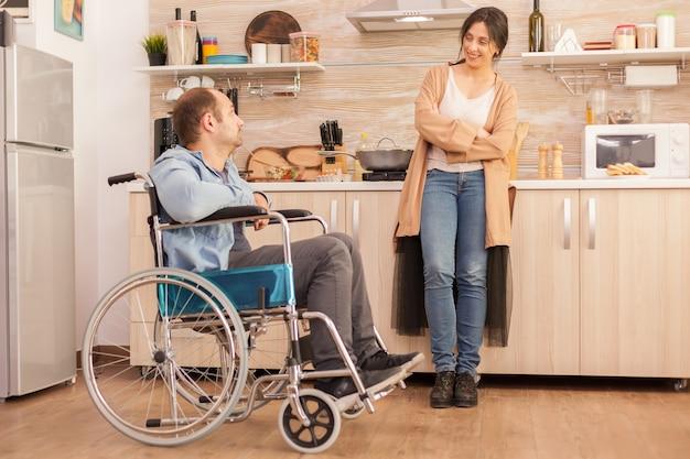 Frau, die behinderten ehemann im rollstuhl anlächelt, während sie mit ihm spricht. behinderter, gelähmter, behinderter mann mit gehbehinderung, der sich nach einem unfall integriert.