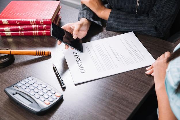 Frau, die bei dame smartphone bei tisch mit dokument, taschenrechner und stift zeigt