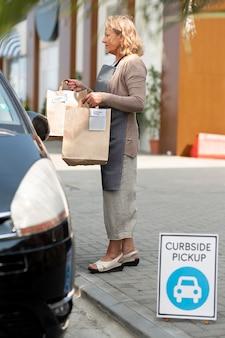 Frau, die bei einer abholung am straßenrand eine bestellung aufgibt