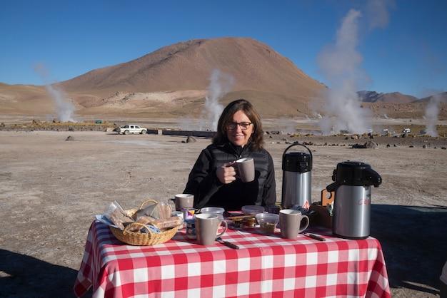 Frau, die bei el tatio, calama, san pedro de atacama, provinz el loa, antofagasta regio frühstückt