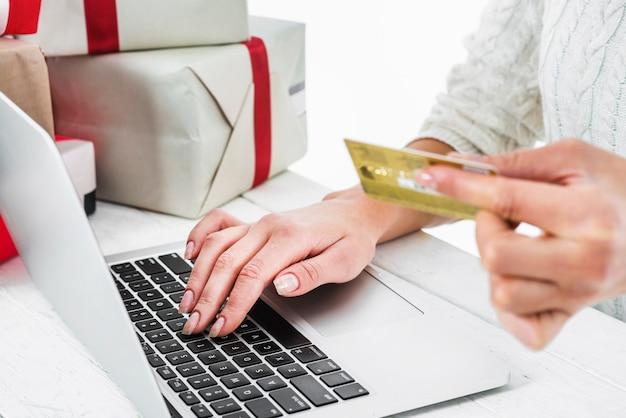 Frau, die bei tisch kreditkarte verwendet