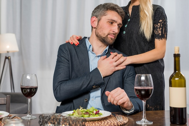 Frau, die bei tisch mann mit platte und gläsern umarmt