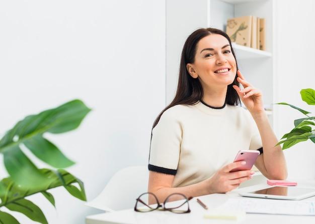 Frau, die bei tisch mit smartphone im büro sitzt