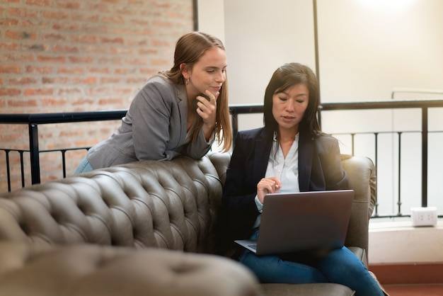 Frau, die beiläufig ideen auf sofa an modernem arbeitsplatz bespricht