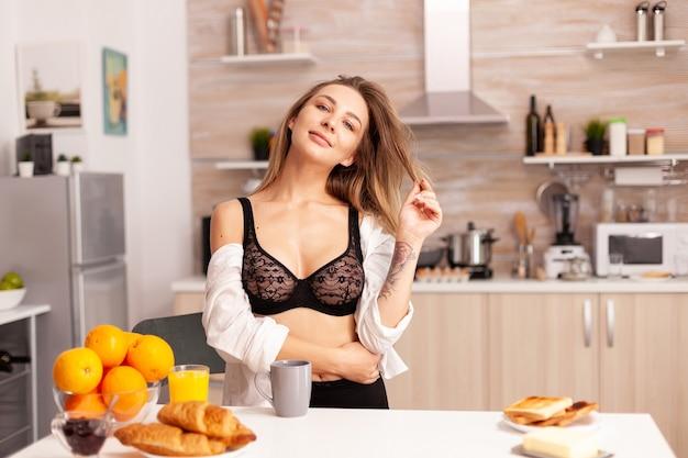 Frau, die beim frühstück in der hauptküche mit haaren spielt und sexy unterwäsche trägt. junge attraktive frau mit tätowierungen in verführerischer unterwäsche, die eine tasse tee in der küche lächelnd hält.